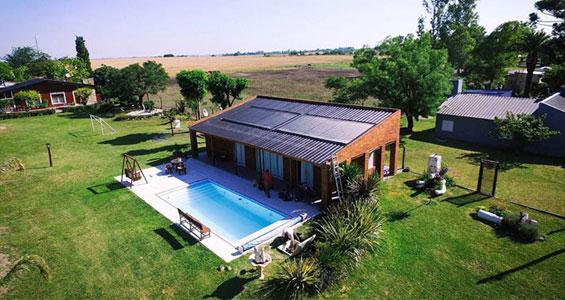 Una casa con un amplio jardín que usa placas solares para calentar el agua de la piscina con energía solar