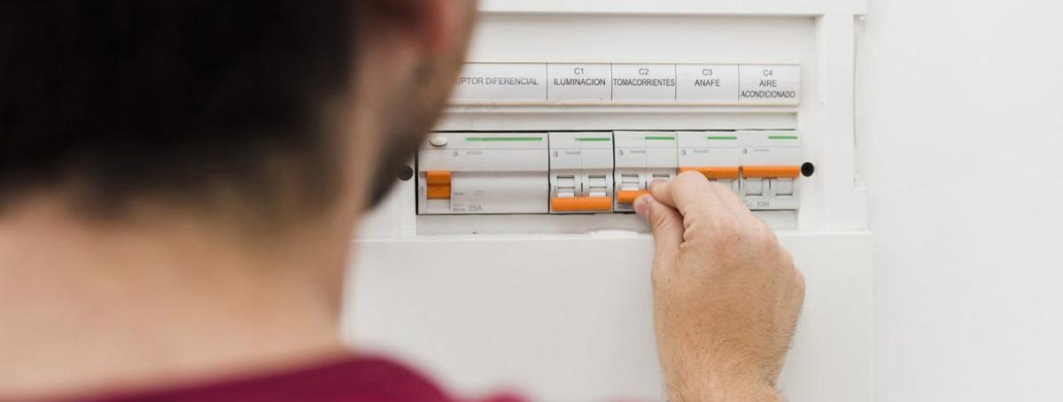 Un hombre joven mirando el cuadro eléctrico tras una de las verificaciones eléctricas periódicas
