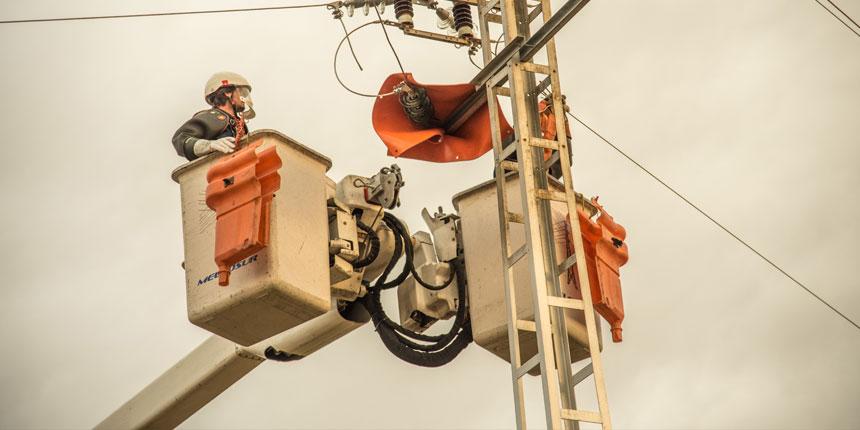 Dos operarios de Melfosur realizando servicios energéticos en una línea aérea eléctrica