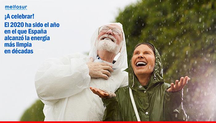 Un hombre mayor y una mujer disfrutando de la lluvia en un bosque en referencia a la apuesta por las energías renovables en España