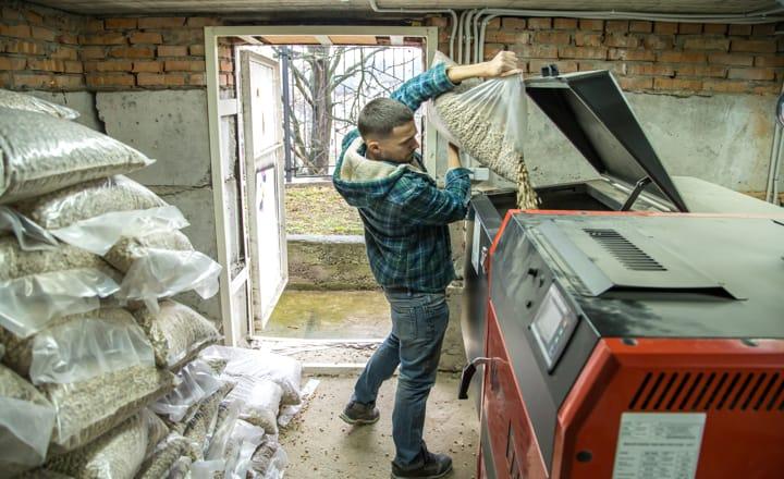 un hombre echando pellets en una estufa de biomasa